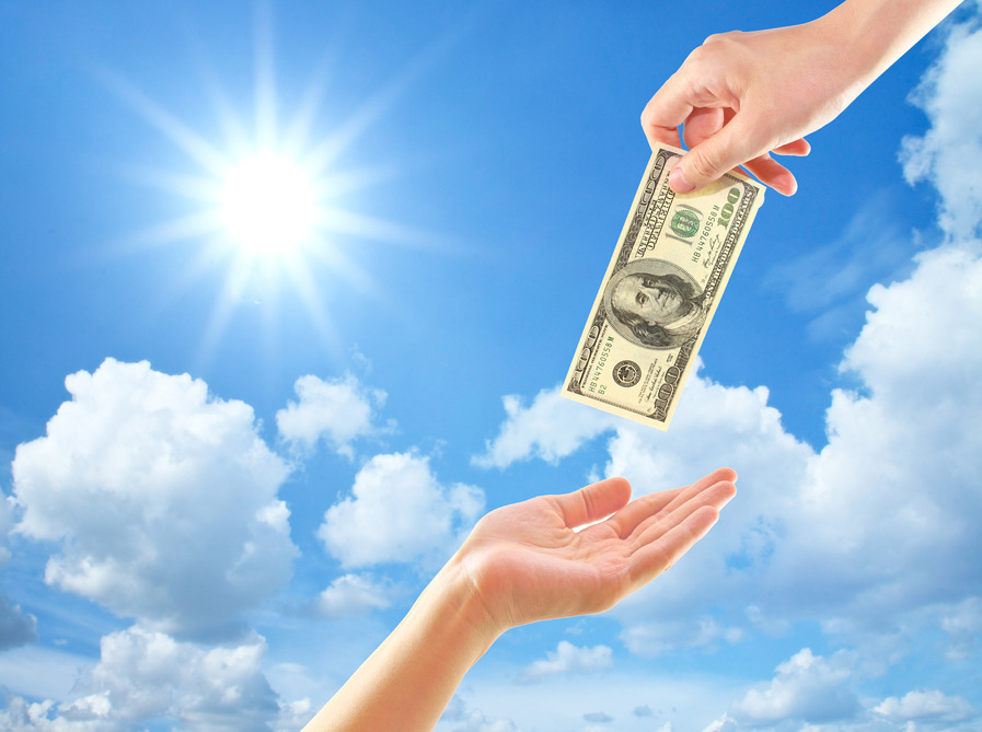 Hand giving money to other hand over clouds and sun
